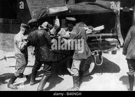 events, First World War / WWI, medical service, severely wounded French soldier is being loaded on an ambulance - Stock Photo