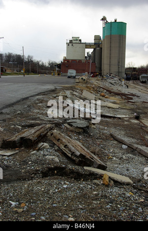Uprooted railroad ties litter tracks leading to a grain elevator - Stock Photo