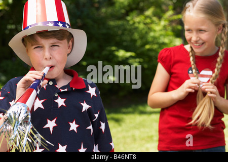 Portrait of Boy Wearing Stars and Stripes Top and Hat, Blowing Noisemaker Horn, Girl Watching - Stock Photo