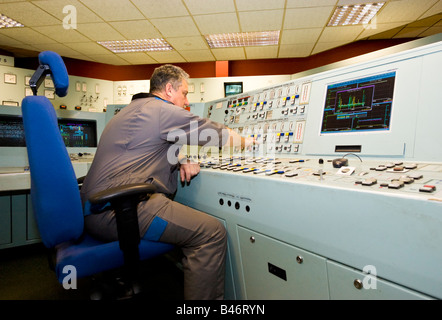 Engineer in overalls operates a large complex console in the hi tech control room of a UK Power Station - Stock Photo