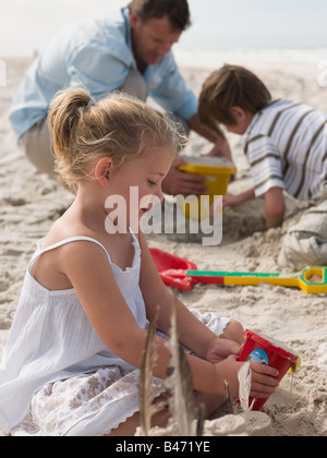 Family playing in sand - Stock Photo