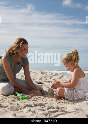 Mother and daughter playing in sand - Stock Photo
