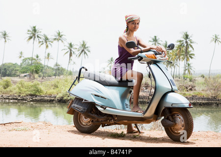 Young woman on moped - Stock Photo
