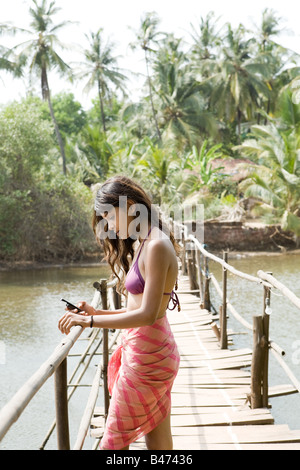 Young woman on bridge with cellphone - Stock Photo