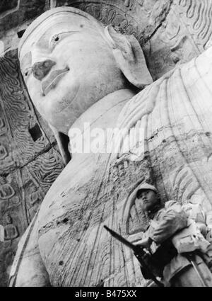 geography / travel, China, politics, Chinese guard in front of a Buddha statue, Yungang Grottoes, after the occupation - Stock Photo