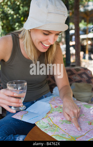 Young woman looking at map - Stock Photo