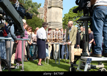 BBC TV The Antiques Roadshow expert and public with film crew filming with an antique dolls house at Wells Somerset - Stock Photo