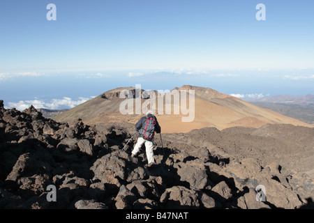 A walker negotiating the traverse over a magma field at the start of the walking route from Teide down over the - Stock Photo