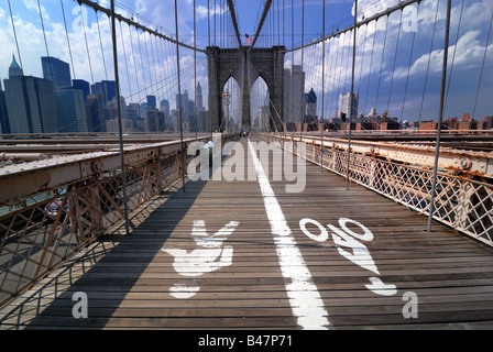 The walkway across the Brooklyn Bridge in New York city has separate lanes for pedestrian walkers and bicyclists. - Stock Photo
