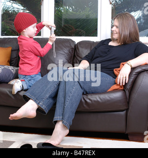 A young boy three and a half years old taking a photo of his Mum in their lounge room at home - Stock Photo
