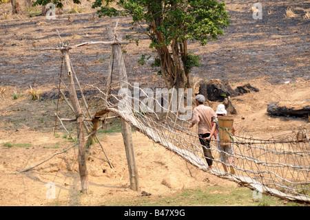 Vietnamese couple crossing a rope bridge Central Highlands Vietnam - Stock Photo