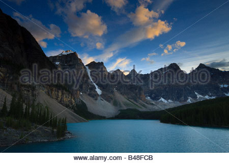 Strong winds blow cumulus clouds over the Canadian Rockies and Moraine Lake at sunset. - Stock Photo
