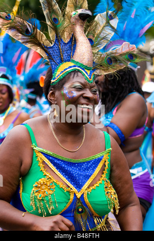 London , Notting Hill Carnival parade , smiling portly middle aged black woman in peacock costume dances in pageant - Stock Photo