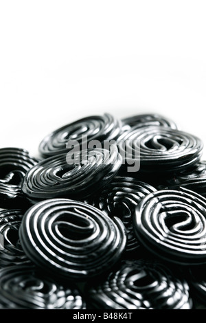 Rolls of tasty liquorice candy rolls isolated on white - Stock Photo