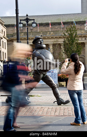 Tourist taking a photograph of Desperate Dan statue in the city centre,Dundee UK - Stock Photo
