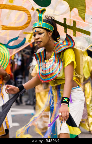 London , Notting Hill Carnival parade , pretty smiling happy exotic young  black girl dancer in Egyptian style fantasy - Stock Photo