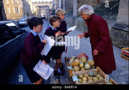 Boys try out their French in the local market - Stock Photo