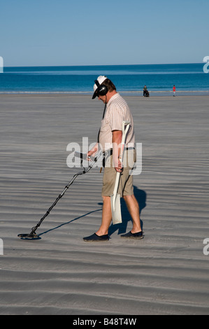 Man with metal detector and spade looking for lost objects on Cable Beach near Broome Western Australia - Stock Photo