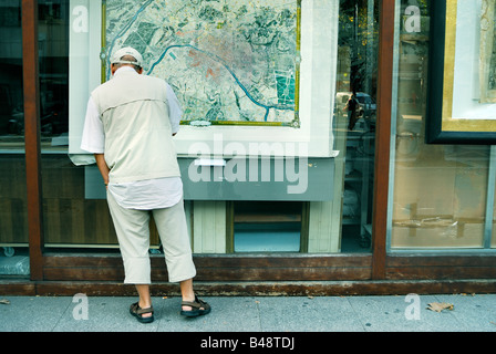 Paris France, Shopping Man Window shopping Looking at Old Map of Paris in Shop Window, Viaduc des Arts - Stock Photo
