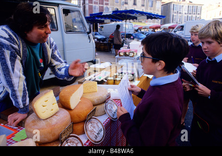 Boys try out their French at a cheese stall in the local market - Stock Photo