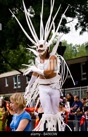 London , Notting Hill Carnival parade , man in white costume with spiked head & fingers dances on stilts - Stock Photo
