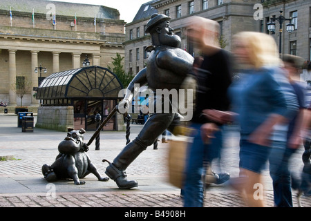 Motion blur while pedestrians are walking past Desperate Dan in Dundee city centre UK - Stock Photo