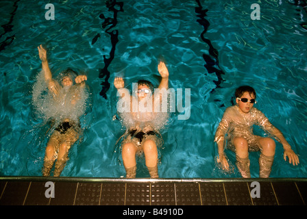 Primary school boys wearing goggles push off at the beginning of a back-stroke race in a swimming pool - Stock Photo