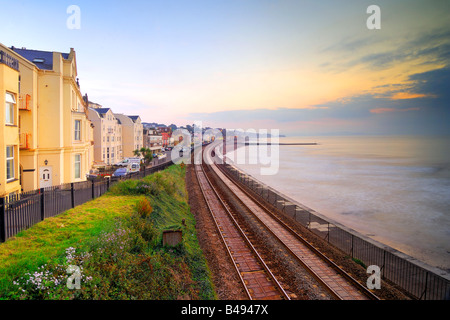 Sunrise from the railway footbridge at Dawlish in South Devon looking up the railway track towards Dawlish station - Stock Photo