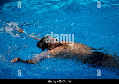 A man swimming in a private swimming pool - Stock Photo