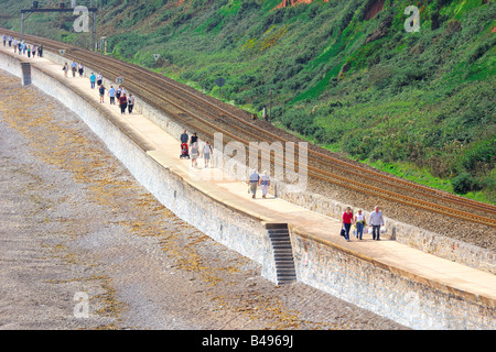 Tourists walking along the seafront promenade beside the railway track between Dawlish and Dawlish Warren in South - Stock Photo