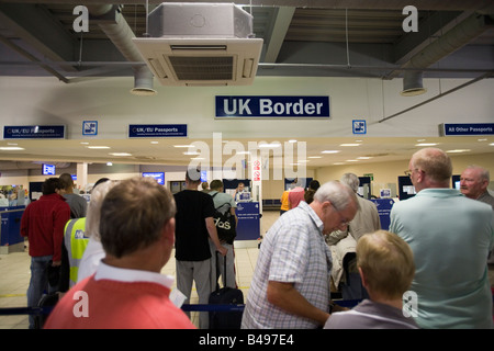 People queuing at immigration UK border, Luton Airport, England, Britain, Europe. - Stock Photo