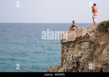 A MAN TAKES A PHOTO OF HIS FRIEND ON THE EDGE OF A ROCK OVERLOOKING THE SEA AT NISSI BEACH, CYPRUS. - Stock Photo