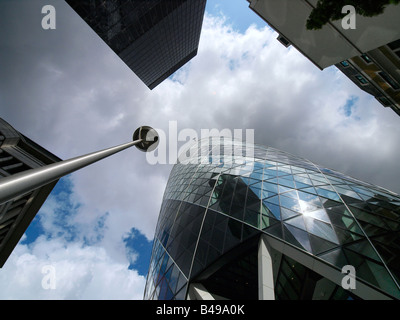 Looking up in the London City dynamic image with Gherkin building and nice clouds - Stock Photo