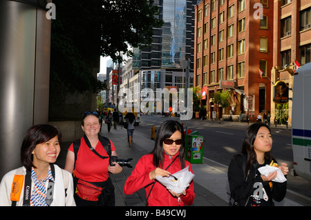 Group of female tourists walking on Front Street in downtown Toronto eating chips - Stock Photo