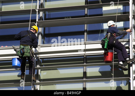 Window cleaners abseiling a corporate building in a U.K. city. - Stock Photo