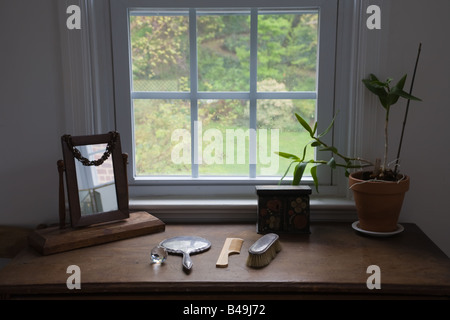 Still-life with wooden dresser, comb, brush, jewelery box, mirror and plant, with a window overlooking a wet autumn - Stock Photo
