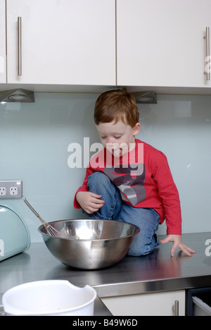 Boy three and a half years old sitting on kitchen bench eager to lick the cake mixture bowl - Stock Photo