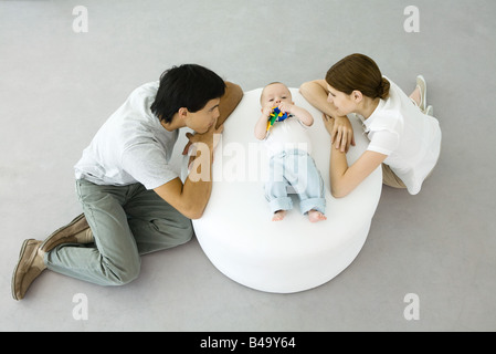 Young parents leaning against ottoman, looking at baby lying between them - Stock Photo