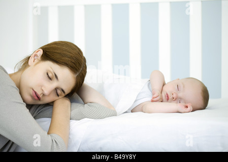 Mother resting head beside sleeping infant, eyes closed - Stock Photo