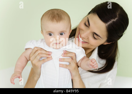 Mother holding baby, smiling - Stock Photo