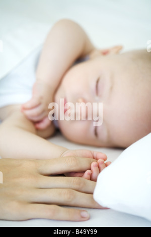 Adult holding sleeping baby's hand, cropped view - Stock Photo