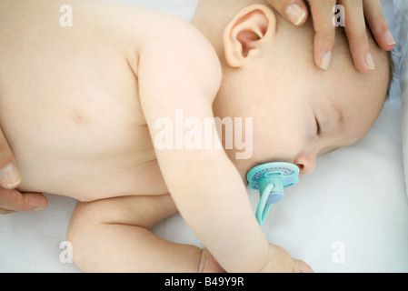 Mother stroking sleeping baby's head, cropped view - Stock Photo