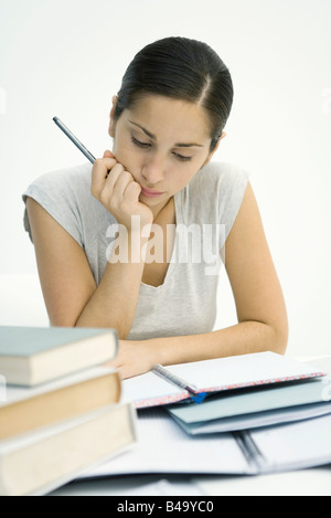 Young woman sitting with stack of books, studying notebook - Stock Photo