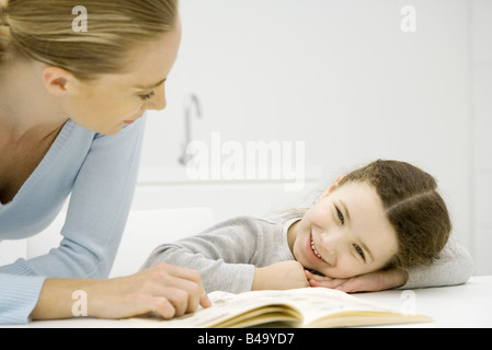 Mother and daughter looking at book together, girl resting head on arms - Stock Photo