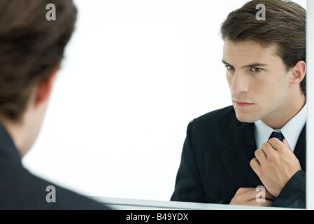 Businessman looking at self in mirror, adjusting tie - Stock Photo