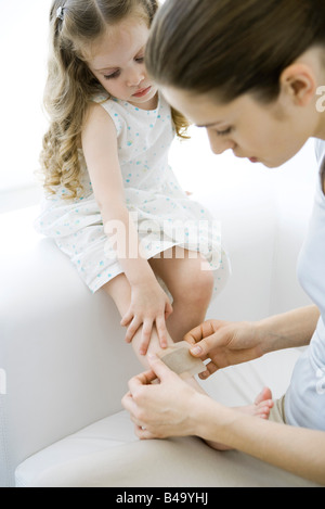 Mother putting adhesive bandage on young daughter's leg - Stock Photo