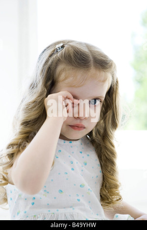 Little girl rubbing her eye, looking at camera - Stock Photo