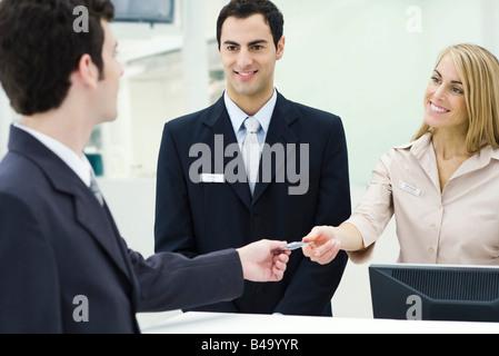Man giving credit card to smiling customer service representatives - Stock Photo