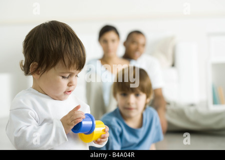 Toddler girl playing with toys, family watching in background - Stock Photo