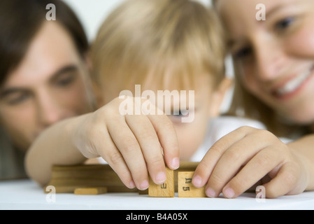 Little boy arranging game pieces, parents watching - Stock Photo